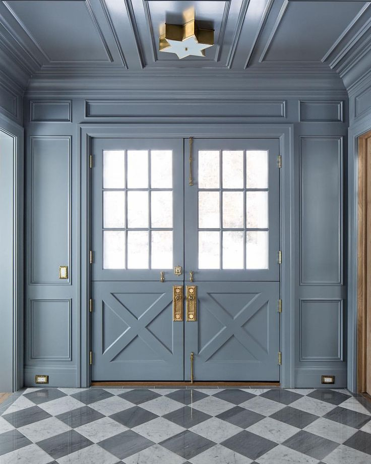 Blue grey painted paneling in a traditional home's entry with checkered flooring. Design by The Fox Group. #paneling #thefoxgroup #bluegray #entry #brasshardware