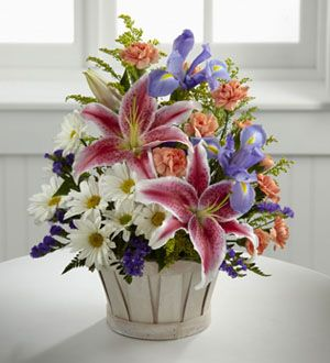 The FTD® Wondrous Nature™ Bouquet is bountifully bedecked with a dazzling display of color and beauty. Stargazer lilies stretch their fuchsia petals out amongst an arrangement of blue iris, white traditional daisies, orange mini carnations, purple statice, and yellow solidago in a round whitewash handled basket, creating a delightful bouquet your special recipient will adore.