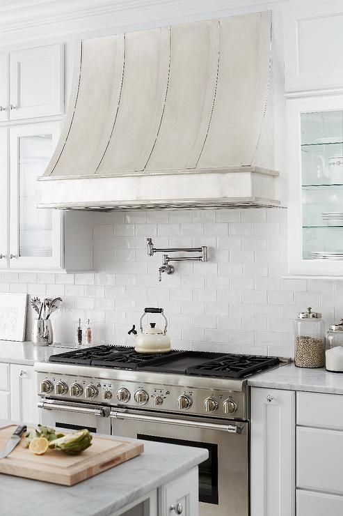 A burnished nickel kitchen hood by Thomas Traders stands over a satin nickel swing-arm pot filler mounted on a linear white glazed tile backsplash and a stainless steel stove.