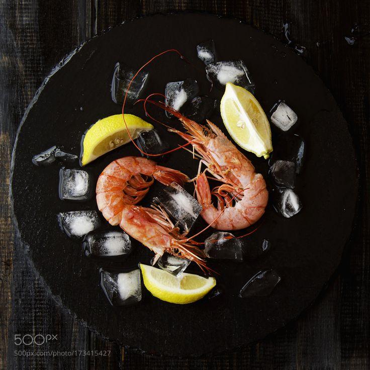 Two raw prawns with lemon and ice cubes selective focus by ViktoriaAgureeva
