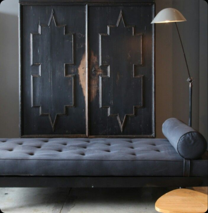 Stunning worn black armoire juxtaposed against modern tufted daybed and industrial modern floor lamp. LOVE.