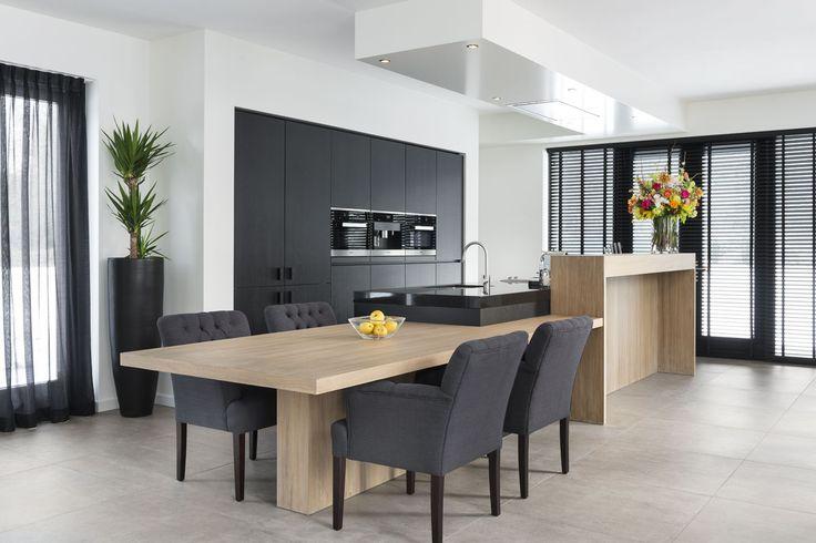 Een strakke, moderne keuken die toch gastvrij en gezellig is en bovendien perfect aansluit bij het interieur door het ingetogen ontwerp en materiaalgebruik.