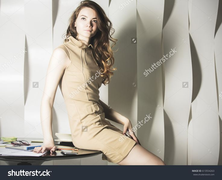 Young business woman sitting on table in office