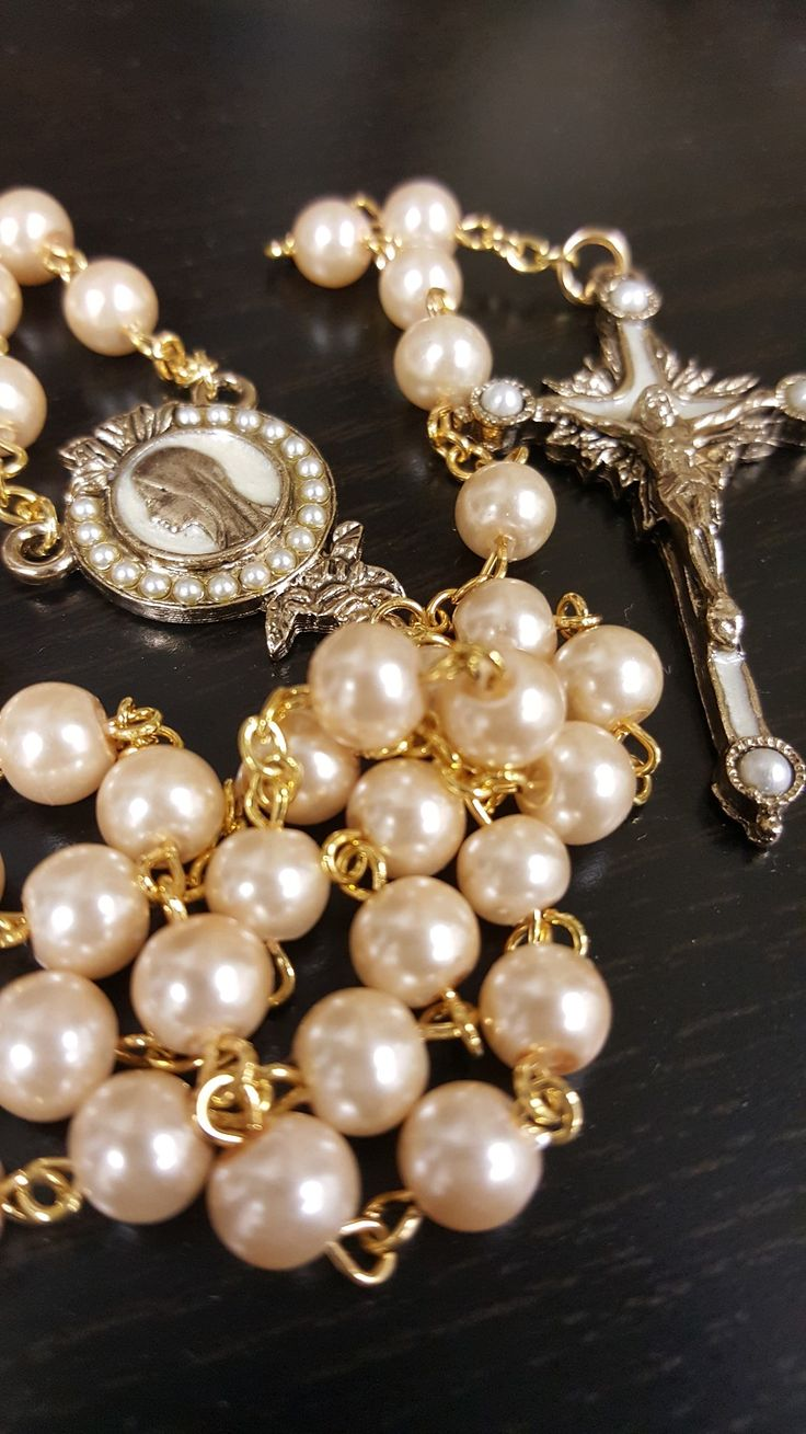 The Pearls of Mary rosary showcases a striking profile of Our Lady, who is surrounded by pearls. The elegant rosary is complete with an ornate crucific featuring white enamel accents. The pearls have a slightly gold overtone, proving you with a feminine and eye catching piece. As you move your fingers along each bead you with notice the smooth silky texture, as you fall deeper into prayer.