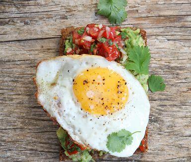 Galet god smörgås med krämig avokado under ett stekt ägg med rinnig gula. Snåla för guds skull inte på tomatsalsan, den gör hela skillnaden! Avokadomackan är perfekt som lättare lunch.