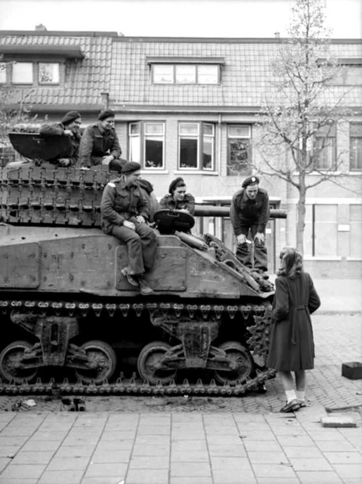 A Canadian Infantry tank crew of the South Alberta Regiment, part of the 4th Canadian Division, chat with a local Dutch girl following the l...