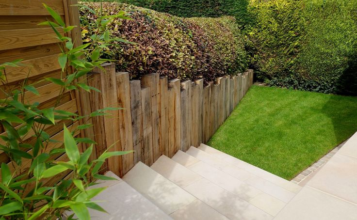 After Redesign & Landscaping - transition from upper to lower level sawn sandstone, bull nose steps, sandstone,setts, vertical sleeper wall, garden screens, bamboo, low maintenance garden