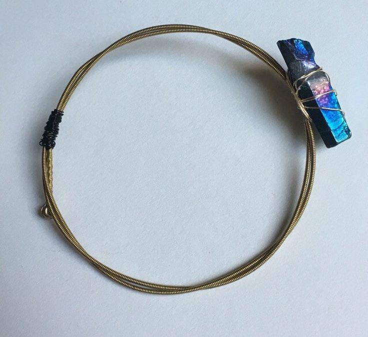 Stand out from the rest with this unique piece! A USA-shaped raw chunk of blue titanium quartz is wire wrapped onto sturdy brass guitar strings twisted to form a bangle bracelet. www.etsy.com/shop/industrialcrystals