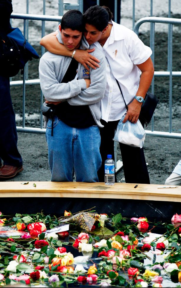 Families and friends of victims embrace next to the flower-covered reflecting pool at the base of the World Trade Center site on the sixth anniversary of the September 11, 2001 attacks.