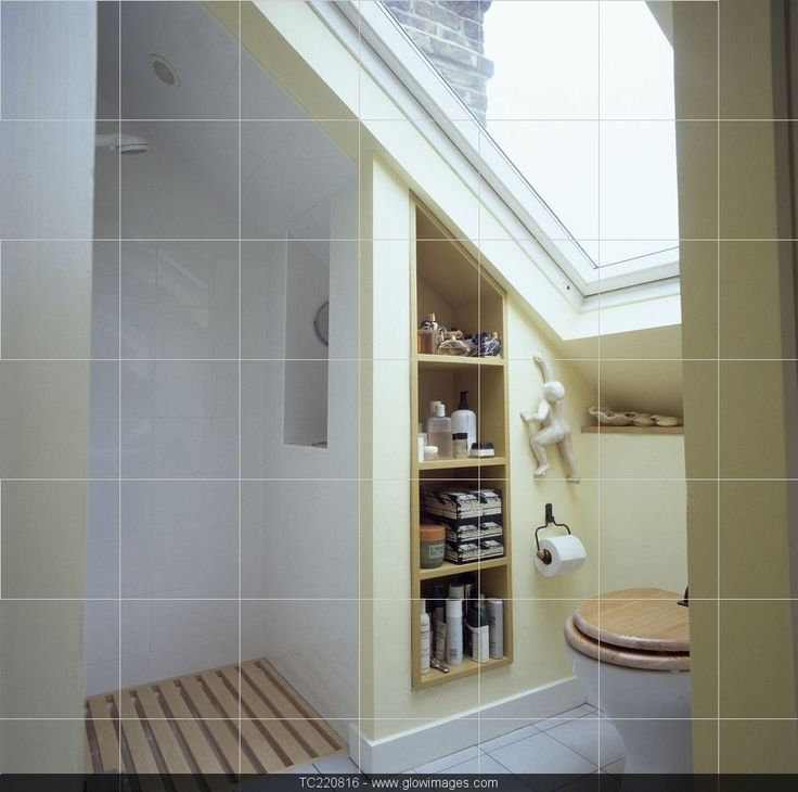 Velux window above toilet in small attic bathroom with open shower and recessed shelving