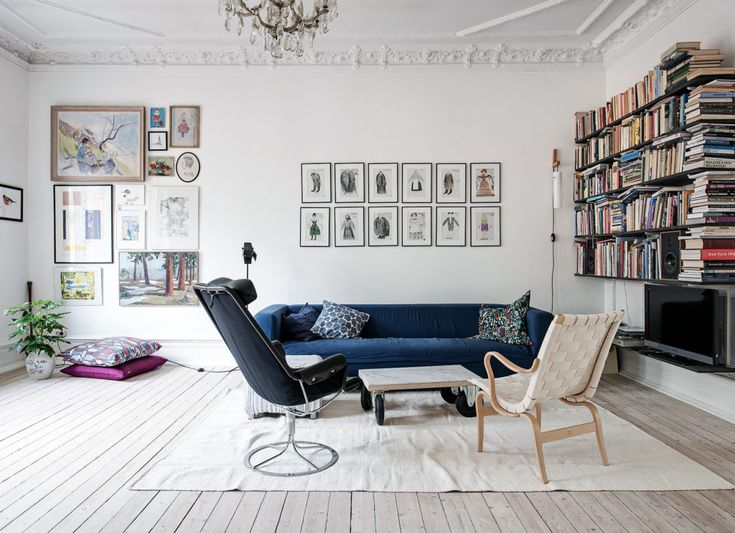 White livingroom, art wall, blue sofa. Scandinavian interior styling and ideas how to decorate the blue sofa.
