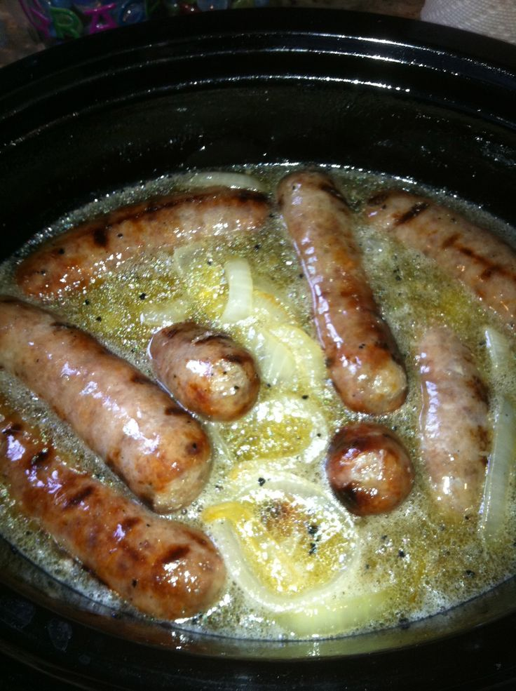 For 12 Brats, you need 2-3 Vidalia onions, 1 stick of butter, 1/4 cup apple cider vinegar, 2 beers, and a couple of dashes of Worcestershire sauce. While grilling the brats on all sides, sauté the onion with butter over medium-high heat. Then layer the onions and butter on the bottom of the crockpot, put the brats on top of those, and then add the beer, apple cider vinegar, and Worcestershire sauce. Simmer on low for 2-3 hours.