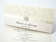 "The ""Ivory Embossed"" invitation is created on quartz DL folded card, layered with beautiful embossed paper and finished off with an oraganza/satin ivory ribbon and diamante buckle  This wonderful wedding invitation can be printed on a selected range of cards and modified to suite your color theme or individual events (whether it be a wedding, engagement or any other special occasion)"