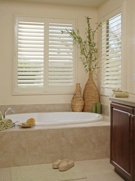 I love the tall plant in the corner...great idea! Plantation shutters by the tub