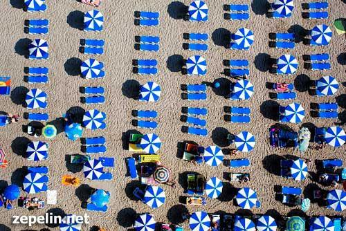 Fotografia aerea de una playa de Valencia repleta de sombrillas