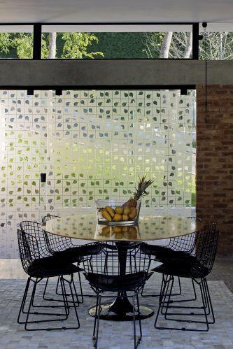 Espaço de jantar teve o mobiliário definido pelo casal de proprietários: cadeiras Bertoia e mesa Saarinen. No piso da casa em Nova Lima (MG), assinada por Bruno Santa Cecília, pedra portuguesa polida e, ao fundo, o painel de vidro serigrafado