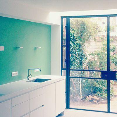 Groene wand in keuken, mooi met stalen kozijn en witte kastjes