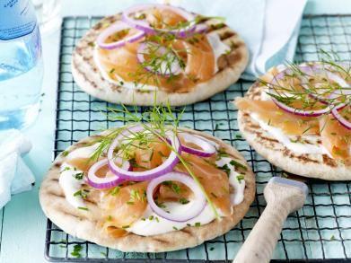 Snelle pizza met gerookte zalm: 200 g gerookte zalm 1 rode ui 1 el gehakt bieslook 100 ml zure room 4 pitabroden 1 el olijfolie