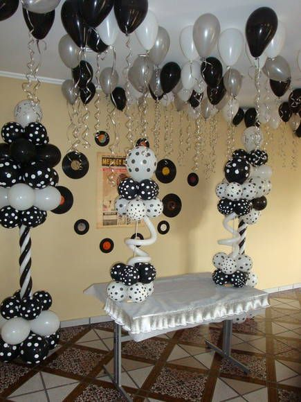 A festival in black and white. Balloon centerpieces with color matching balloon ceiling.