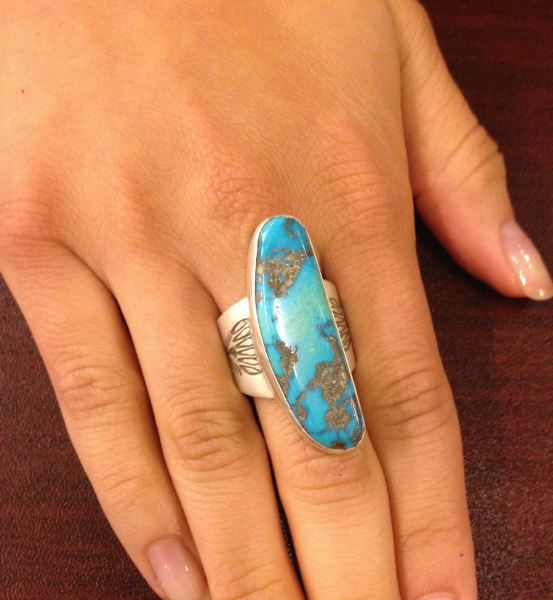 "Lot 335 in the August 20th online & live auction! Beautiful sterling silver ring with Southwestern style design. Featuring large oblong shaped Sleeping Beauty turquoise stone. Band has pressed repousse style design. Marked ""EB sterling"" consignor states this is made by Ed Begay. #Fashion #Jewelry #POGAuctions"