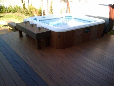 To make it look like part of the deck, stain the deck to match the hot tub, and then partially sink it...like!