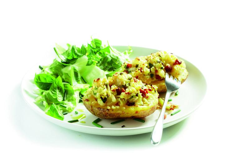 k de spekblokjes licht krokant in een hete koekenpan. Halveer de aardappelen. Haal het aardappelkruim er voorzichtig uit en schep dit met het sjalotje, de mosterd, yoghurt, bieslook, zout en peper door de spekjes. Schep dit mengsel in de uitgeholde aardappelen en strooi de kaas erover. Zet de gevulde aardappels in een lage ovenschaal en zet ze even onder een hete ovengrill of in de nog hete oven tot de kaas gesmolten is.
