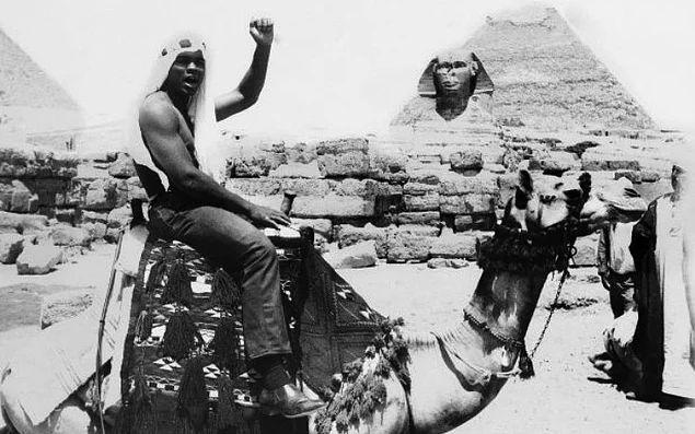 Muhammed Ali, Mısır ziyareti sırasında bir deve üzerinde Siyah Güç Selamı verirken, 1964.