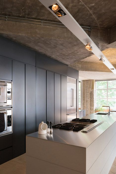 Concrete ceiling beams and columns have been exposed during the renovation of this central London apartment.
