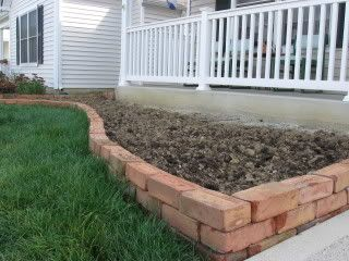 """I like the idea of having a brick border along the fences - It can be straight or wavy like this photo.  It can be raised up then a foot or so (6-12"""").  I'm liking this idea for next Spring... Also, could use bricks just to border the walkway to the house in the front and back of the house ... Make it cohesive with the front.... Yes...."""