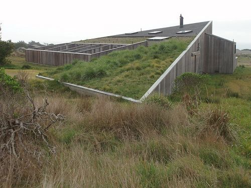 A view of the Brunsell House completed in 1985 at the Sea Ranch.  The sod roof rises from the landscape without obstructing the view of the meadow. Western facing windows provide sweeping views of the Pacific Ocean off the Mendocino Coast.