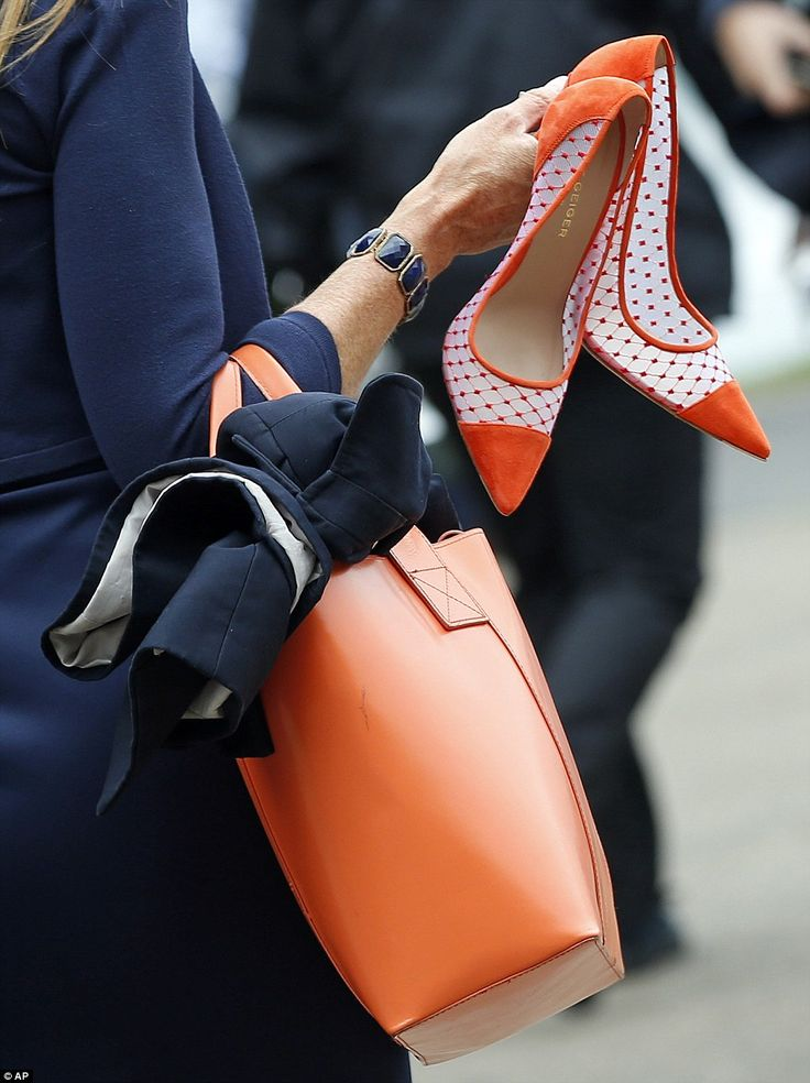 Perfectly matched: A female racegoer arrives carrying her orange court shoes and clutching a similarly bright tote handbag