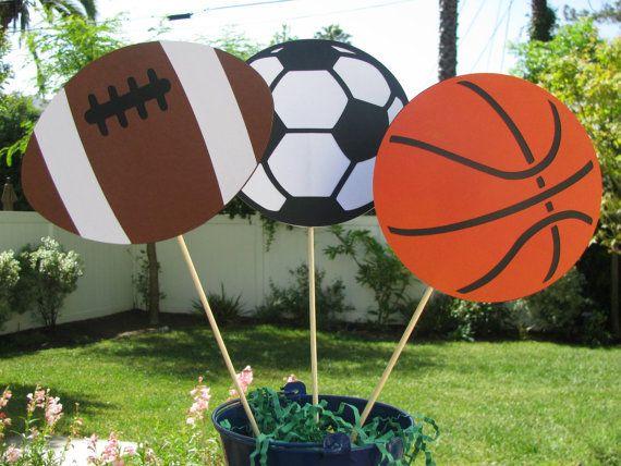 Set de 3 décorations de Table de sport. Chaque boule est environ 5 1/4 po de diamètre, le football est 6 1/2 « x 4 1/2 » et le bâton est long de 7.  Vous recevrez un de chaque : football, ballon de football et de basket-ball, ou vous pouvez indiquer une préférence de nimporte quelle combinaison.  -Simple-face. Face arrière est blanc ou noir avec le bâton entre les couches.  -Conteneur non inclus  Assurez-vous de noter vos choix dans les « notes de vendeur » quand votre achat le...