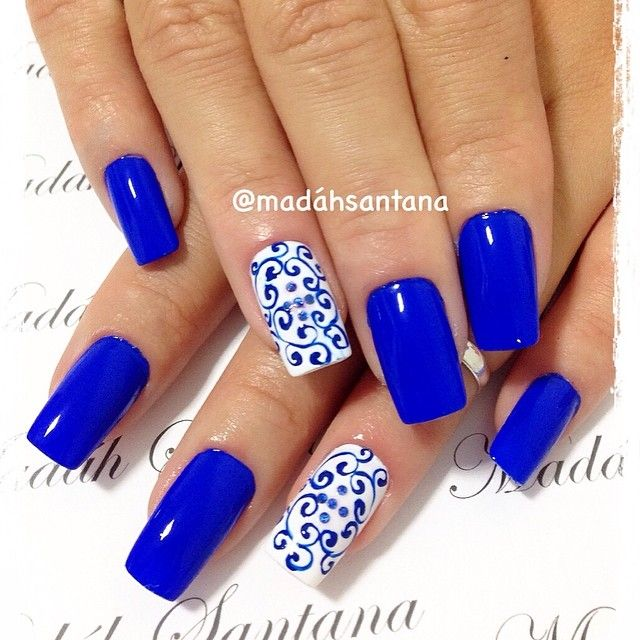 Blue nails with white and blue scrolled accent nail.