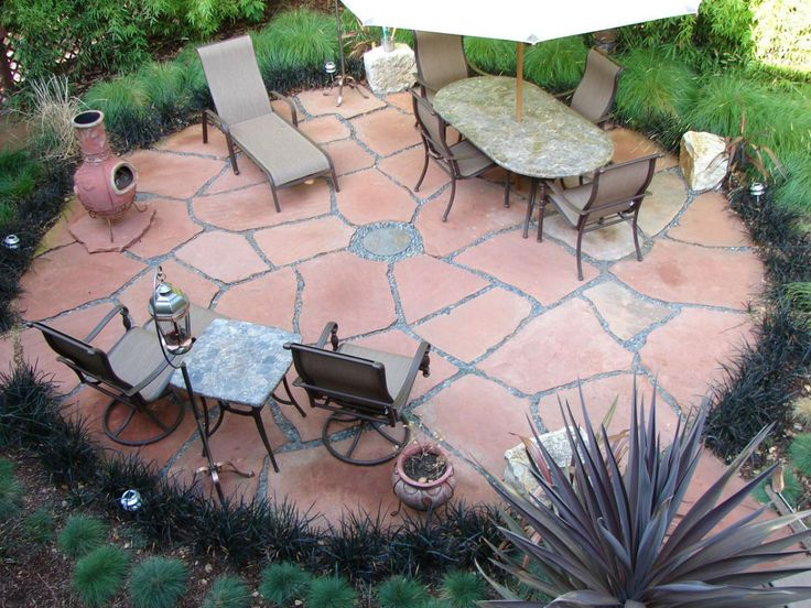 There are good times to be had on this round patio.The outdoor dining and lounge area allows guests a space to enjoy the outdoors. Made of flagstone, it features lounge chairs, floor lamps, a stand-alone antique stove and a table with umbrella shade.