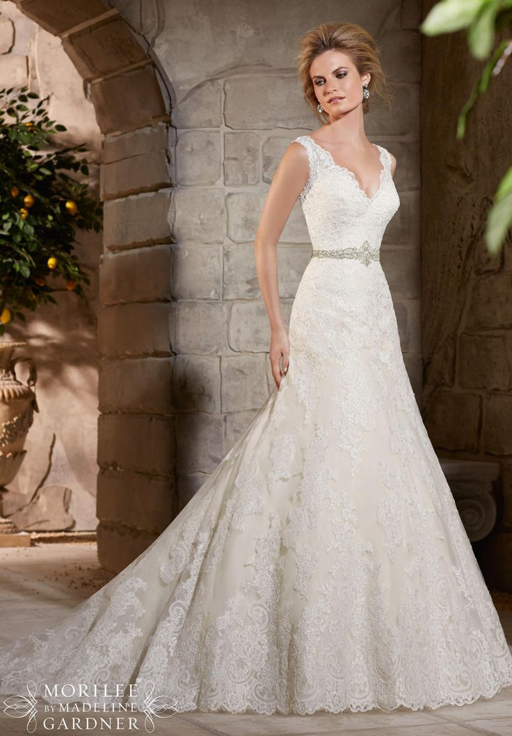 Lace, A-line wedding dress with a beaded belt and straps. Classic, romantic wedding dress.