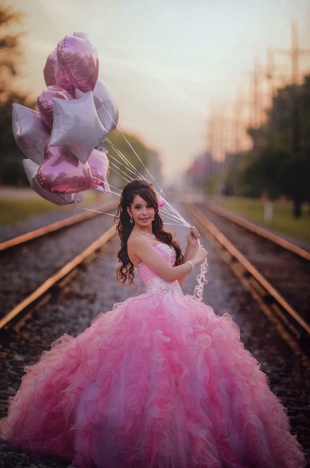Perfect background scenery.. with the train tracks.. the heart and star shaped balloons make it even better.. perfect combination for this quinceañera photograph
