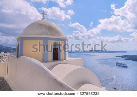 Picturesque traditional greek domed church at Firostefani and beautiful caldera and vulcano on background.Santorinini (Thira) island.Cyclades.Greece.Europe.