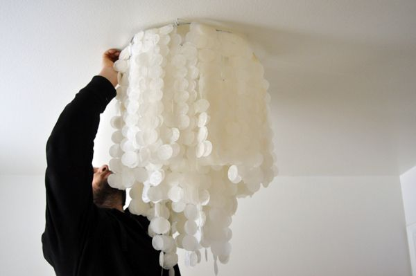 Looks like capiz shells. Chandelier made from wax paper and an old