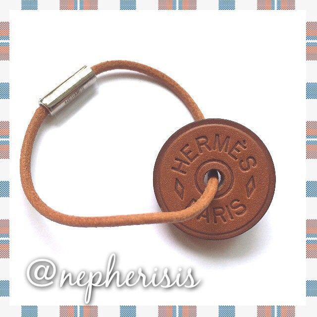 Hermes Token bag charm or key holder in Fauve Barenia. Comes with Hermes box and ribbon.