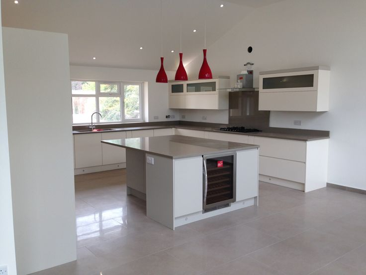 Contemporary, high gloss white kitchen. Beautifully finished with red light shades.