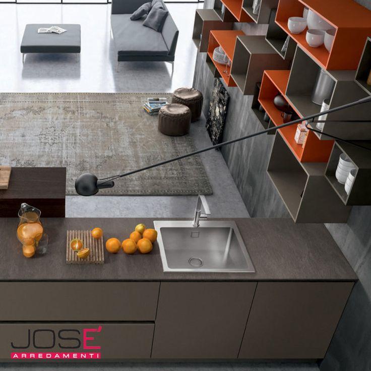 Cucina con parete colonne attrezzata, penisola e bancone piano snack. Finitura laccato opaco.