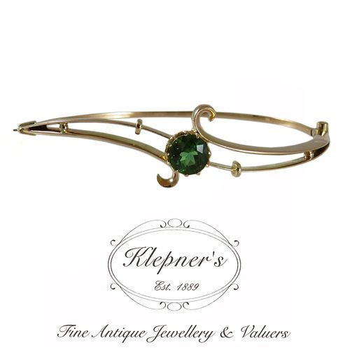 18ct rose gold gold antique Edwardian green tourmaline double-bar hinged bangle, centrally twelve claw set with one 1.55ct round cut green tourmaline & featuring scroll detail. Visit us at www.klepners.com.au