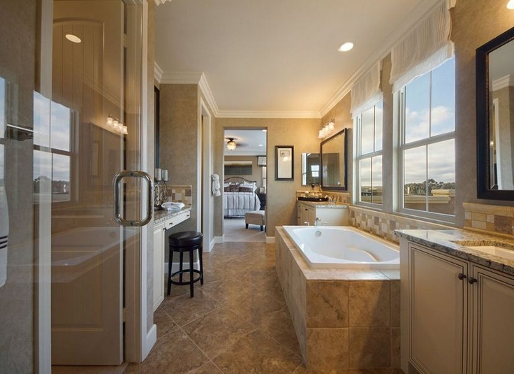 A spacious bathroom connects the walk in closet and the for Pictures of master bathrooms in new homes