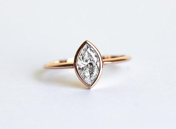 Classic solitaire marquise shape diamond engagement ring in 18k solid gold. Sparkly half carat diamond. This design is simple and easy to stack with