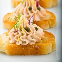 Easy to make and prepare ahead for entertaining, smoked salmon whipped into a creamy mousse and piped into crisp crostini