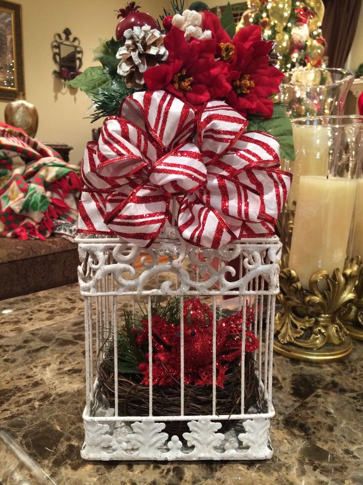 Plane bird cage I bought at Michaels added Christmas picks, poinsetta flowers, made bow, all bought at Michaels. Birds nest bought last year from Kirklands. I love how it turned out