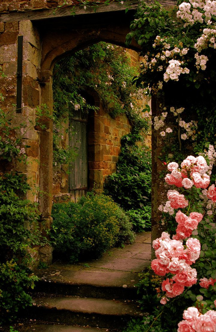 Flowers In The Wall Garden - An arched doorway covered w pink white flowers leads into a plant covered space which we imagine is also stunning