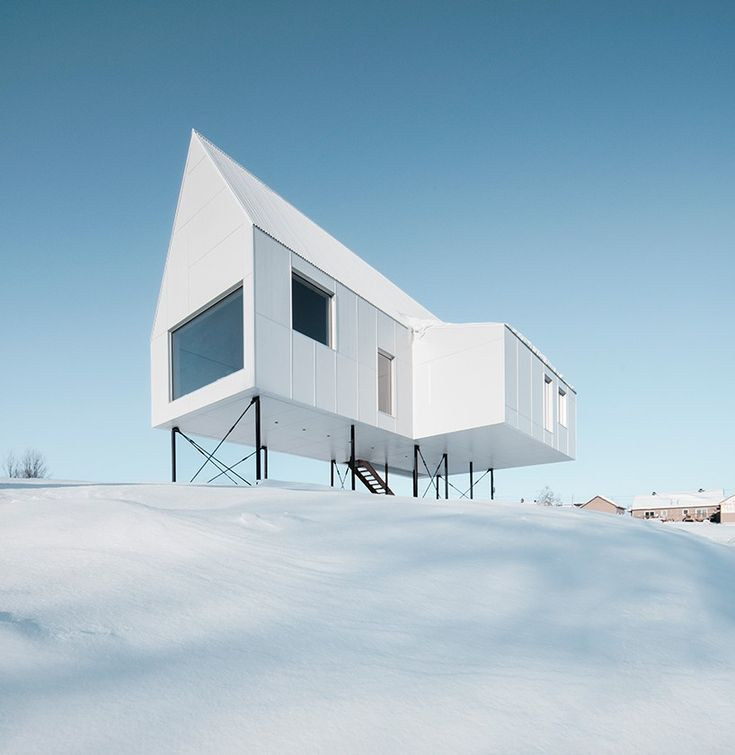 Standing proud of the snow covered hills of Quebec, Canada, this bright white gabled house acts as a private chalet for its owners!