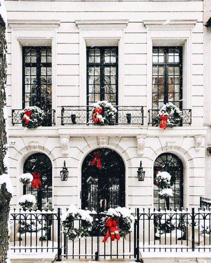 Beautiful City House Christmas Decoration For Outdoors. White Christmas With Greenery And Red Ribbons And Bows For The Festive Holiday Spirit.