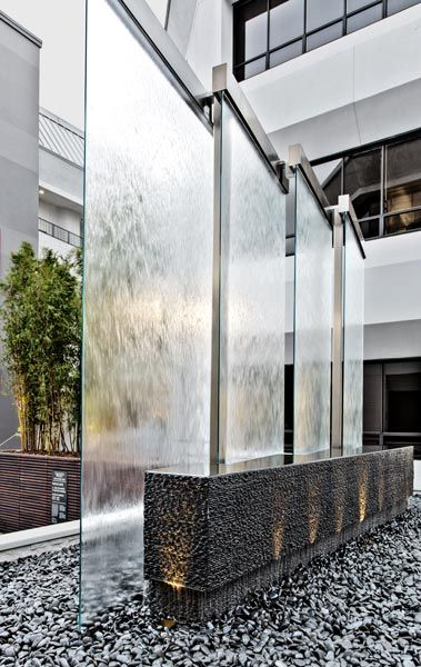 Glass water wall and stone feature in an exterior lounge.